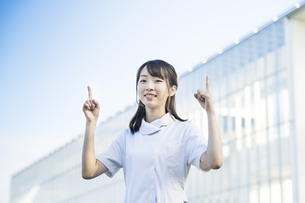指差しポーズをする白衣の女性の写真素材 [FYI04849625]