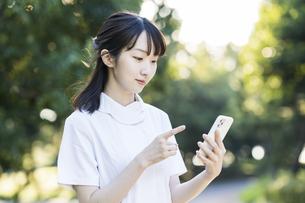 スマートフォンを持つ白衣の女性の写真素材 [FYI04849634]