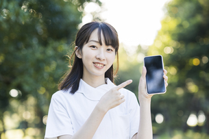 スマートフォンを持つ白衣の女性の写真素材 [FYI04849636]