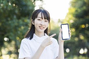 スマートフォンを持つ白衣の女性の写真素材 [FYI04849637]