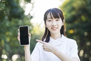 スマートフォンを持つ白衣の女性の写真素材 [FYI04849638]