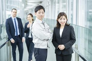 作業服姿とスーツ姿のビジネスチーム男女の写真素材 [FYI04850201]