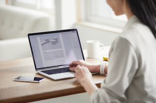 ノートパソコンを開き仕事をする女性の写真素材 [FYI04850599]