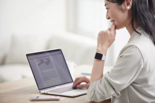 ノートパソコンを開き仕事をする女性の写真素材 [FYI04850620]