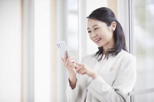 スマートフォンを見るスーツを着た女性の写真素材 [FYI04850628]