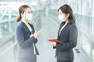 マスクをつけて立ち話するビジネスウーマンの写真素材 [FYI04850913]