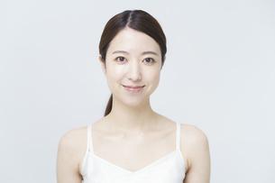 白いキャミソールを着て微笑む女性の写真素材 [FYI04850915]