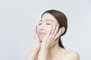 美容イメージ・顔を触る女性の写真素材 [FYI04850924]