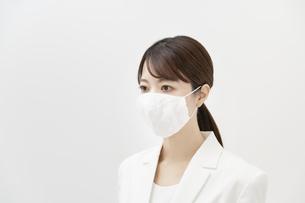マスクを着ける白いスーツ姿の女性の写真素材 [FYI04850993]