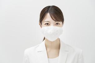 マスクを着ける白いスーツ姿の女性の写真素材 [FYI04850994]