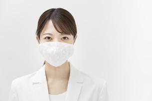 マスクを着ける白いスーツ姿の女性の写真素材 [FYI04850995]