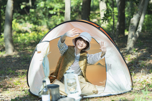 ソロキャンプイメージ・テントの中から笑顔で手を振る若い女性の写真素材 [FYI04851494]
