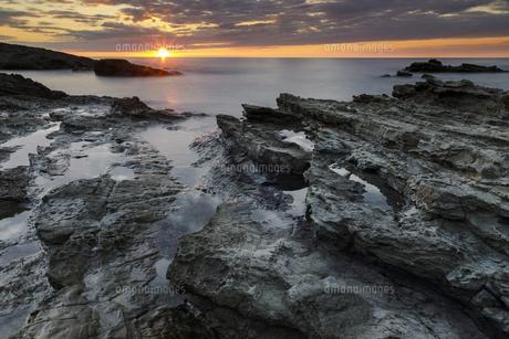 油戸の岩礁帯と日本海に沈む夕陽の写真素材 [FYI04851499]