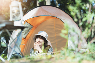 ソロキャンプイメージ・テントの中で寝転ぶ若い女性の写真素材 [FYI04851508]