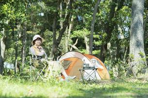 ソロキャンプイメージ・テントの前でくつろぐ若い女性の写真素材 [FYI04851521]