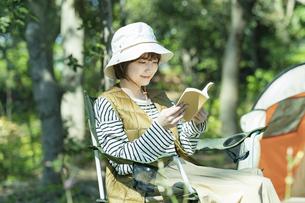 ソロキャンプイメージ・本を読む若い女性の写真素材 [FYI04851649]