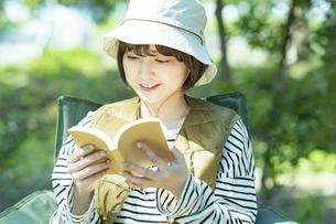 ソロキャンプイメージ・本を読む若い女性の写真素材 [FYI04851651]