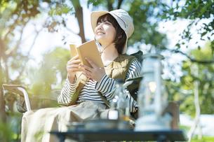 ソロキャンプイメージ・本を読む若い女性の写真素材 [FYI04851655]