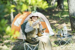 ソロキャンプイメージ・スマートフォンを操作する若い女性の写真素材 [FYI04851664]