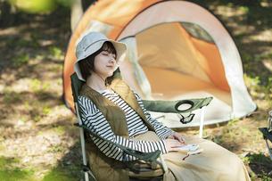 ソロキャンプイメージ・テントの前で昼寝する若い女性の写真素材 [FYI04851667]