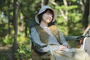 ソロキャンプイメージ・テントの前で昼寝する若い女性の写真素材 [FYI04851669]