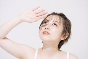 まぶしい太陽光を手でさえぎるアジア人の若い女性の写真素材 [FYI04851702]