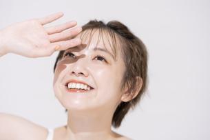 まぶしい太陽光を手でさえぎるアジア人の若い女性の写真素材 [FYI04851703]