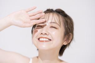 まぶしい太陽光を手でさえぎるアジア人の若い女性の写真素材 [FYI04851704]