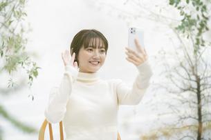 スマートフォンを使ってビデオ通話する女性の写真素材 [FYI04851709]