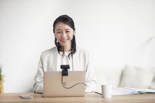 ノートパソコンを開きリモート会議をする女性の写真素材 [FYI04851870]