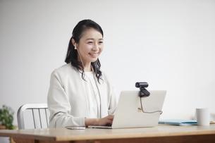 ノートパソコンを開きリモート会議をする女性の写真素材 [FYI04851879]