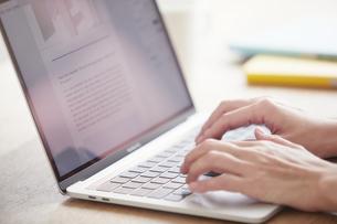 ノートパソコンを開き仕事をする女性の手元の写真素材 [FYI04851899]