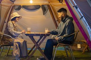 テントの中で語らう男女の写真素材 [FYI04852024]