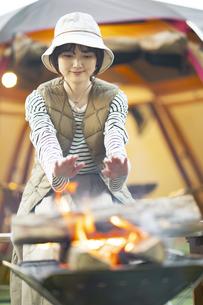 焚き火を楽しむ女性の写真素材 [FYI04852069]