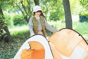 キャンプのためにテントを準備する女性の写真素材 [FYI04852072]