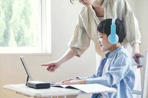 ヘッドホンをしてタブレット端末を見ながら勉強する男の子と女性の写真素材 [FYI04852254]