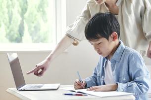 ノートパソコンを見ながら勉強する男の子と女性の写真素材 [FYI04852259]