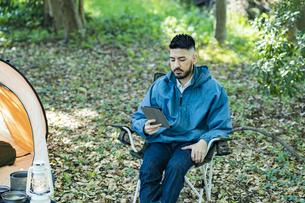 ソロキャンプイメージ・タブレット端末の画面を見る男性の写真素材 [FYI04852271]