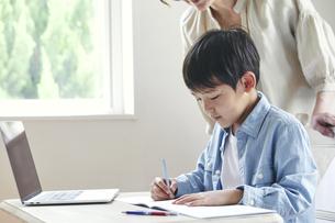 ノートパソコンを見ながら勉強する男の子と女性の写真素材 [FYI04852273]