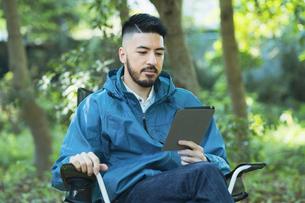 ソロキャンプイメージ・タブレット端末の画面を見る男性の写真素材 [FYI04852277]