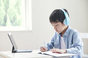 ヘッドホンをしてタブレット端末を見ながら勉強する男の子の写真素材 [FYI04852281]