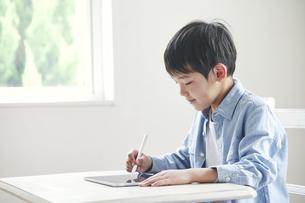 タブレット端末を見ながら勉強する男の子の写真素材 [FYI04852286]