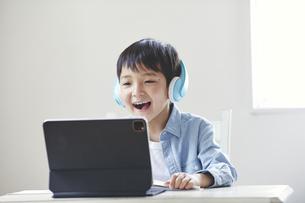 ヘッドホンをしてタブレット端末を見ながら勉強する男の子の写真素材 [FYI04852292]