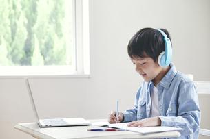 ヘッドホンをしてノートパソコンを見ながら勉強する男の子の写真素材 [FYI04852293]