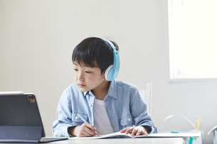 ヘッドホンをしてタブレット端末を見ながら勉強する男の子の写真素材 [FYI04852294]