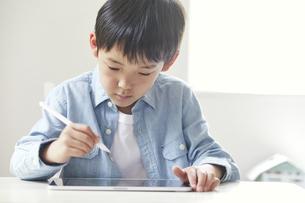 タブレット端末を見ながら勉強する男の子の写真素材 [FYI04852296]