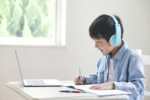 ヘッドホンをしてノートパソコンを見ながら勉強する男の子の写真素材 [FYI04852298]