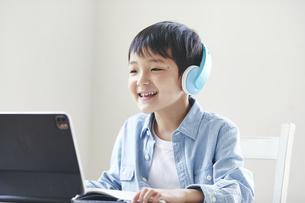 ヘッドホンをしてタブレット端末を見ながら勉強する男の子の写真素材 [FYI04852300]