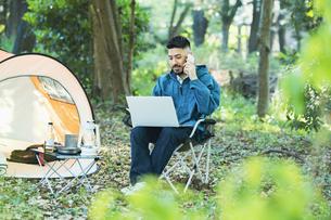 キャンプをしながら仕事をする男性の写真素材 [FYI04852317]