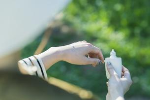 屋外で日焼け止めを塗る女性の写真素材 [FYI04852565]